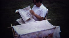 1971: Dad reading newspaper outdoor baby changing table. Stock Footage