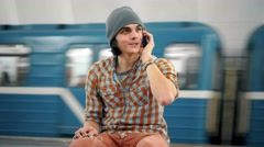 Young caucasian man talking on cellphone on subway platform Stock Footage