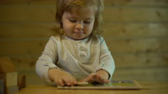 Father helps the child lay down wooden puzzle at the table Stock Footage