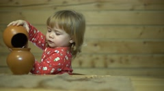 Beautiful curly-haired child in the kitchen playing with utensils Stock Footage