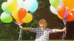 Child jumping with balloons in the park Stock Footage