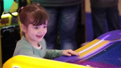Little girl playing air hockey game Stock Footage