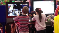 Kids playing shooter video game in game center Stock Footage