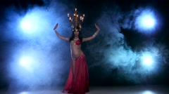 Attractive belly dancer dancing with candles on her head, black, smoke Stock Footage