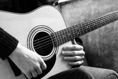 Young man playing an acoustic guitar on the background of a concrete wall Stock Photos