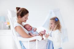 Mother with newborn baby and toddler daughter Stock Photos