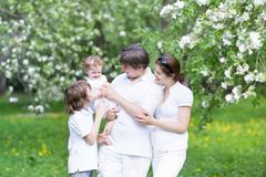 Happy young family in a blooming apple tree garden - stock photo