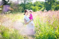 Pregnant mother and her toddler walking in a sunny meadow Stock Photos