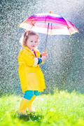 Funny toddler with umbrella playing in the rain Stock Photos