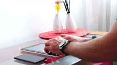 Men with watch, smartphone and smartband typing on tablet in his living room Stock Footage