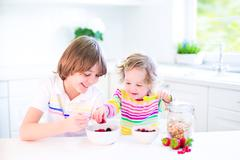 Kids eating fruit and cereal Stock Photos