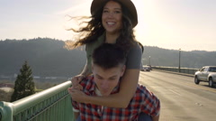 Man Gives His Girlfriend A Piggyback Ride Down St Johns Bridge Stock Footage