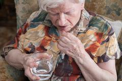 Old woman taking medication Stock Photos
