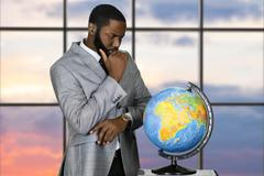 Thoughtful black businessman with globe. Stock Photos