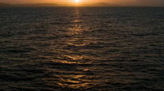 At Sea Sunset Sunrise Tilting Up From Water to Horizon - stock footage
