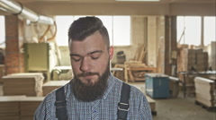 Young carpenter with a beard and a stylish haircut in the workshop. RAW video Stock Footage