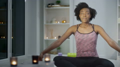 4K Young woman relaxing & meditating at home with many lit candles - stock footage