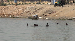 Black african arabic peoples swimming in the dirty water of port - Port Sudan Stock Footage