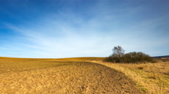 Timelapse of plowed field under blue sky with cirrus clouds.  - stock footage