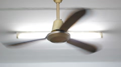 Old style Ceiling fan spins on high setting with light Stock Footage
