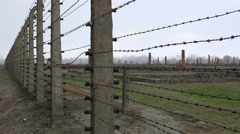 Birkenau barracks ruins through barbed wire - Auschwitz concentration camp Stock Footage