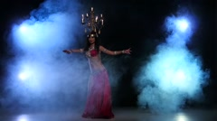 Attractive belly dancer dancing with candles on her head, black, smoke, slow Stock Footage