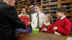 4K Happy family in clothing store buying new school uniforms for the children - stock footage