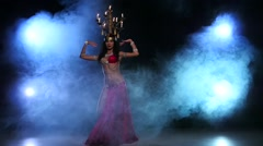 Attractive belly dancer starts dancing with candles on her head, black, smoke Stock Footage