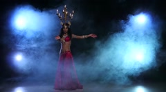 Attractive belly dancer continue dancing with candles on her head, black, smoke Stock Footage