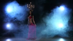 Attractive belly dancer go on dancing with candles, her head, black, smoke, slow Stock Footage