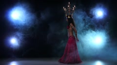 Belly dancer starts dancing with candles, her head, black, smoke, slow motion Stock Footage
