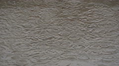 Rain drops falling in puddle, close up, water dropping on flooded city street. - stock footage