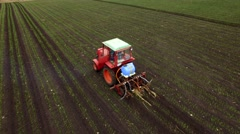 Aerial view of tractor sprays fertilizers Stock Footage