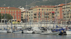 Pan view of people walking by the sailboats anchored in Port Lympia, Nice Stock Footage