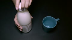 Woman Pouring Milk Into a Blue Cup Stock Footage