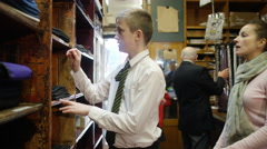 4K Mother shopping with her children in school uniform supply store Stock Footage