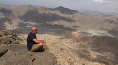 Man sitting on a cliff in the canyon edge - Arkaweet, Sudan - stock footage