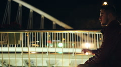 Young man smoking cigarette on a bridge at the night Stock Footage