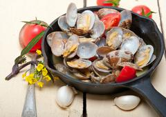 fresh clams on an iron skillet - stock photo