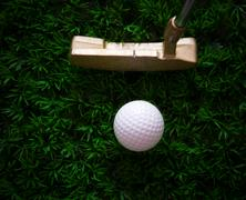golf ball on green grass and putter - stock photo