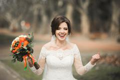 Beautiful bride in the park on her wedding day with bouquet - stock photo