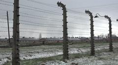 Birkenau barracks through barbed wire - Auschwitz concentration camp, Poland - stock footage