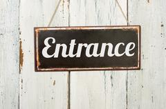 Old metal sign in front of a white wooden wall - Entrance - stock photo