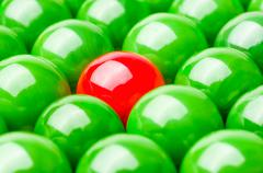 Concept with red and green marbles -  Being different Stock Photos