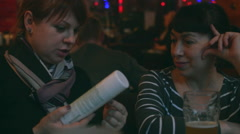 Two Women Sitting at the Bar. One Considers Gifts Stock Footage