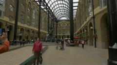Tourists walking and relaxing in Hay's Galleria in London Stock Footage