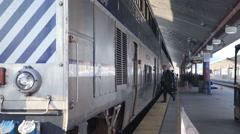 Worker passengers getting onto amtrak metrolink surfrider train Stock Footage