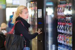 Lady using  a modern vending machine - stock photo