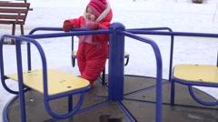 Sweet Newborn Baby Spinning on Carousel in a Winter Day. 4K UltraHD, UHD Stock Footage