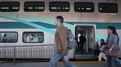 Rush hour passengers stepping onto amtrak metrolink surfrider train - stock footage